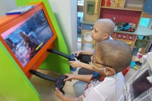 Two young patients play a video game together