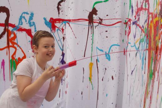 Young patient playing with paint syringe