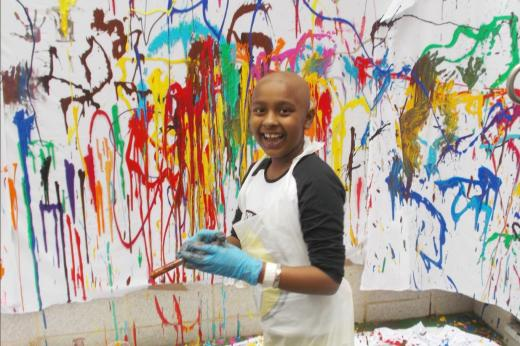 Young patient playing with paint syringes