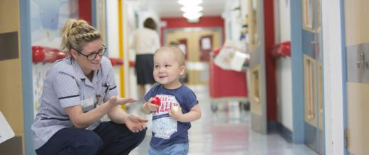 Toddler and nurse in corridor