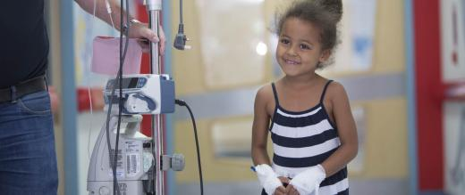 Little girl patient walks corridor linked to medical equipment