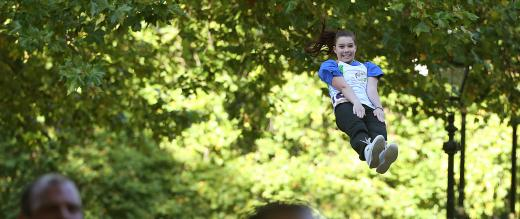 A volunteer thrown in the air as part of cheerleader display at The Royal Parks Half Marathon