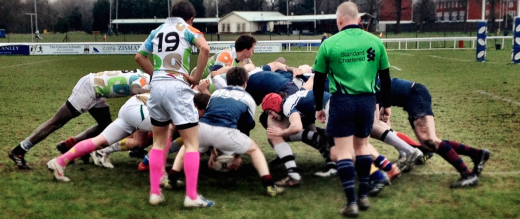 Rugby club charity match players in a scrum