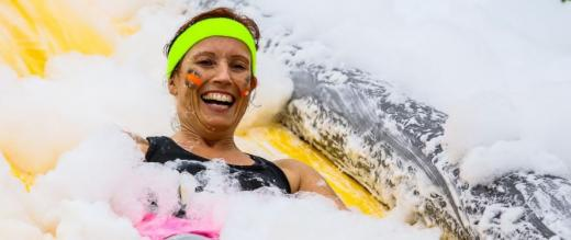 Woman covered in foam on a slide at The Gauntlet Games