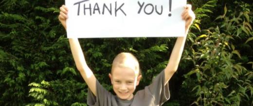 Jim's son Joseph holding up a Thank you! sign