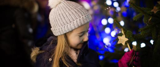 Girl looking at the stars on the Christmas tree