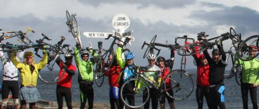 Cyclists raise their bikes at John O' Groats