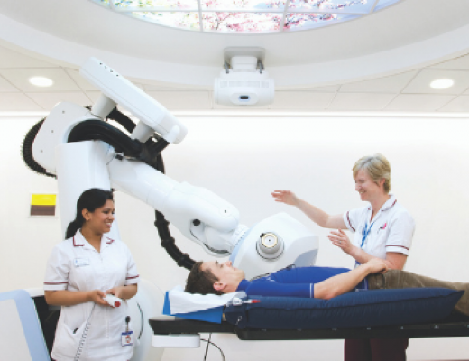 Image of a patient being assessed by two medical staff. The patient is shown the cyberknife.